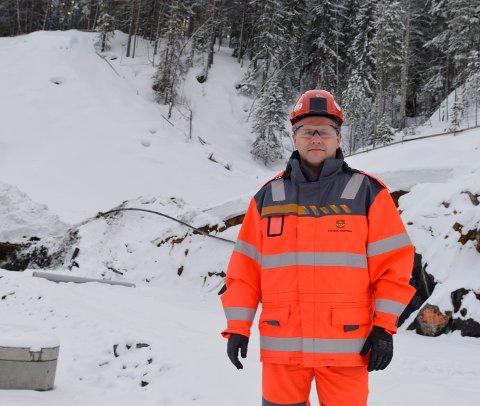 Tom Hedalen, prosjektleder for E134-anlegget, viser til gjerdene bak ham på Moane som er i ferd med å bli helt nedsnødd.