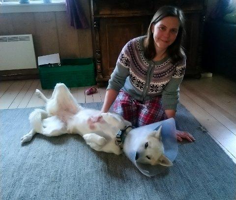 INNEKOS: Etter påkjørselen har Leah stort sett ligget og kost seg foran vedovnen inne. Her sammen med matmor Lise Katrine Haugen Pedersen.