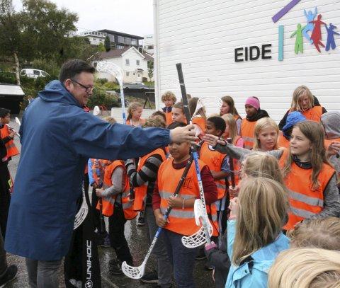 SKIKKELIGE INNEBANDYKØLLER: Elling Allendes fra Karmøy Innebandyklubb deler ut nye køller til elevene på Eide skole.