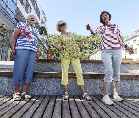 Klare for sommerkonsert: Fra venstre: Hanne Smith, Grethe Ruud og Elin Paulsen i Regnbuenkoret, som i år har flyttet seg til torget fra bølgebryteren. Foto: Pål Nordby