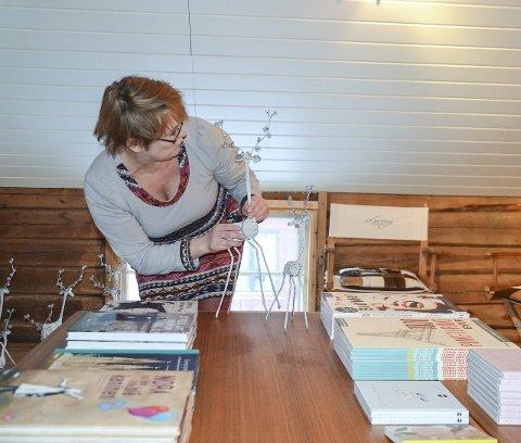 FØR JUL: Sigrid med kvite reinsdyr fra Sør-Afrika. Engler lagd av ekte fjær, kommer også derfra. På bordet et utvalg av bøkene de har i Vintergalleriet. Foto: Guri Jortveit
