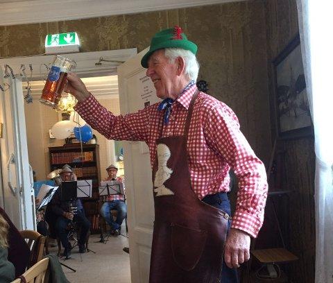 Frivillig ved treffsenteret, Tormod Heiberg, leder an i en tradisjonsskål på oktoberfest.