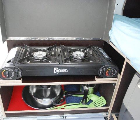 Kokemuligheter: Et uttrekkbart kjøkken med gasskomfyr er skjult under sengen. Her er det også plass til panner, kjeler og annet.