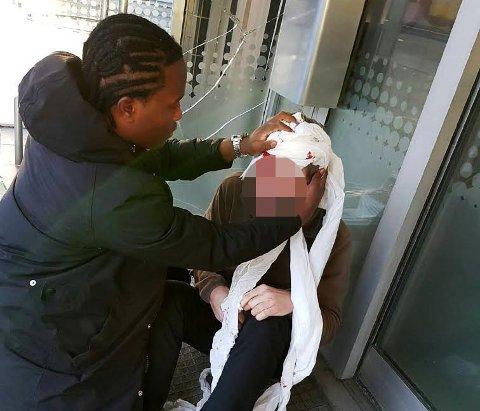 HJELPER: Her hjelper Williams Gomes mannen som fikk et kutt i hodet etter å ha falt inn i et vindu.