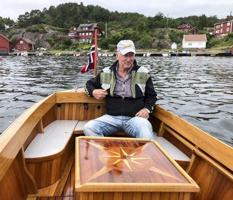 På tur: Frode Berg Stiansen trives godt på fjorden i dette smykket av en båt som han bygde selv i 2009, og utstyrte med en elektromotor.Under kompassrosa skjuler det seg en minibar. Foto: Øystein K. Darbo
