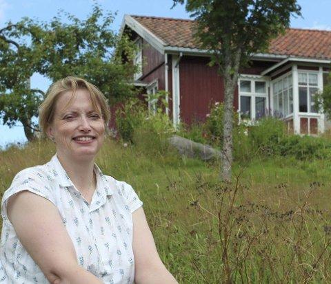 SOMMERTUNET: Leder i Eidskog Museum, Ingrid Brustad har gjort seg godt kjent på bygdetunet allerede, og på den store stubben hviler hun ut mellom øktene.