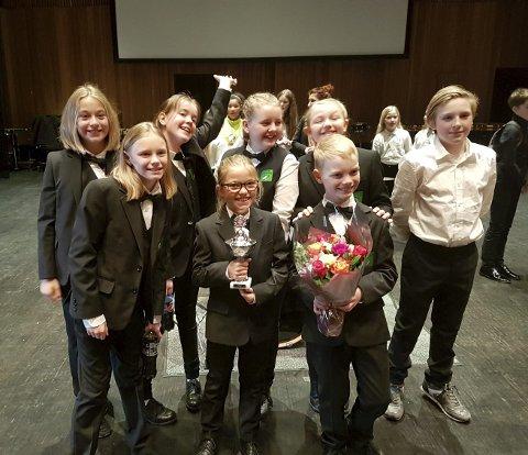 Spilleglede: Skjønhaug skolekorps berømmes for energi og spilleglede, foran ser vi Emily og Thomas med pokal og blomster etter seieren.