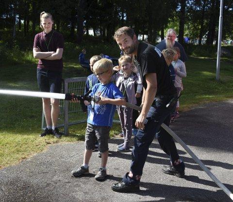 Slangeføring: Christian Bekkesletten lærer hvordan han skal slokke brann ved hjelp av slange og vann. Her med brannmann Bjørn Erland Bakken.