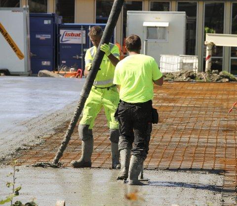 TRØKK I RØRET: Den ferdige betongen kom i strie strømmer. Straks den var ute, var mannskaper på plass for å dra den utover flaten. Foto: Lars Ivar Hordnes