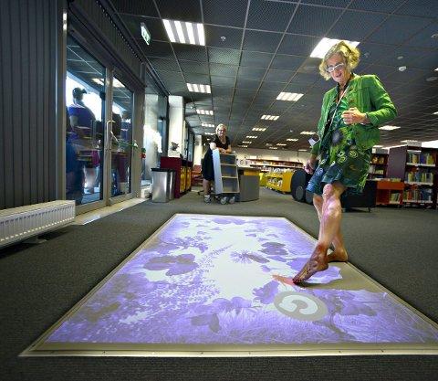 Barnevennlig: Barneavdelingen på Kongsberg bibliotek på Krona har mye mer enn bøker. Her ser vi biblioteksjef Elisabeth Bergstrøm prøve seg på et gulvspill. FOTO: JAN STORFOSSEN
