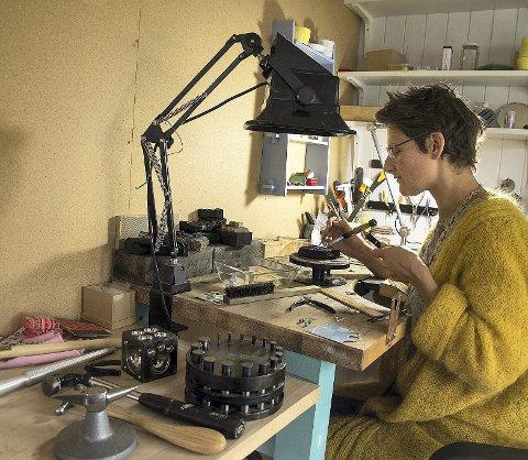 Omgitt av utstyr: En sølvring formes ved verkstedpulten til smykkekunstneren Hadda Bjørkeli. Hun har alt hun trenger innen rekkevidde i det lille huset som tidligere var stall. Alle foto: Kari Kløvstad