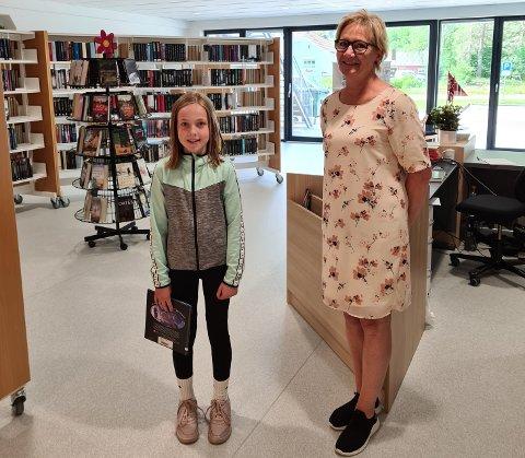 PÅ SPARKET: – Vi bare hopper i det, sier bibliotekar Tone Vasland som har ansvaret både for bibliotek og innbybggertorg på Konsmo og Byremo. Her asammen med Amalie Lislevand som lånte bøker på åpningsdagen på Konsmo.