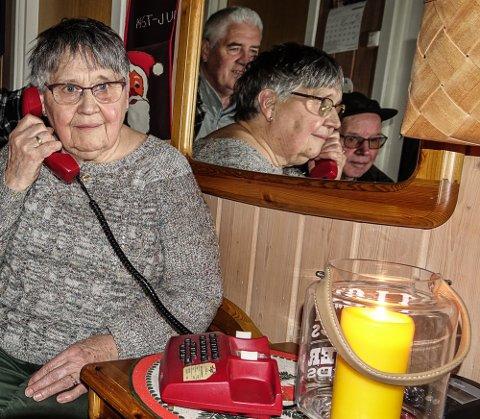 FJERNES IKKE ENNÅ: Britt Rundberget og alle med fasttelefon i Risberget får beholde den til mobildekningen blir bedre. I speilet bak Rundberget ser vi Odd Fylling og Bjørn Bergjordet, også dem beboere i Risberget.