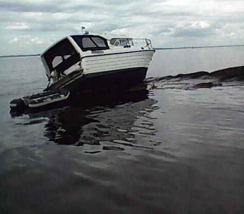 PÅ LAND: Her ligger båten på tørt land. Rundt båten er det en oljeaktig film på vannet.