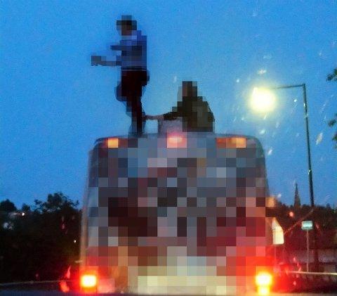 PÅ TAKET: Her står en ung gutt i russeklær på taket av en russebuss i fart, mens en annen ungdom holder ham i leggen.