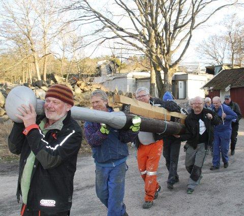 DUGNADSFOLK PÅ LANG REKKE: 2014: Paul Henriksen og Eivind Børresen leder an gjengen som bærer en stolpe som skal brukes i 1814-telegrafen på Skjelsbuveten. FOTO: RITA WIBORG
