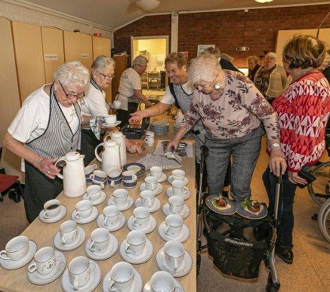 SERVERER: En armada av kaffekopper venter på å bli fylt opp, mens gjestene står i kø. F.v. Karin Hansen, Astrid Tasken, Berit Sommer, mens Reidun Larsen strekker seg frem på høyre side av bordet.