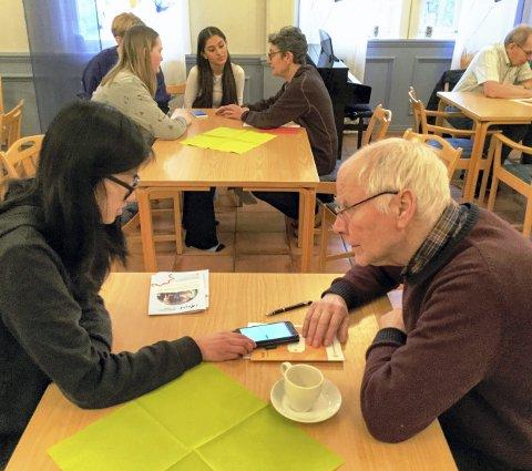 INSTRUKTØR OG ELEV: Pensjonist Bernhard Røed lytter nøye til de råd som tiendeklassingen Malin Katharina Johansen kommer med. Ved hvert bord på Holmen sitter det små «studiegrupper».