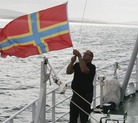 VENSKAPFLAGG: Per Inge Igland heiser Orknøyane sitt flagg på veg inn til Kirkwall.