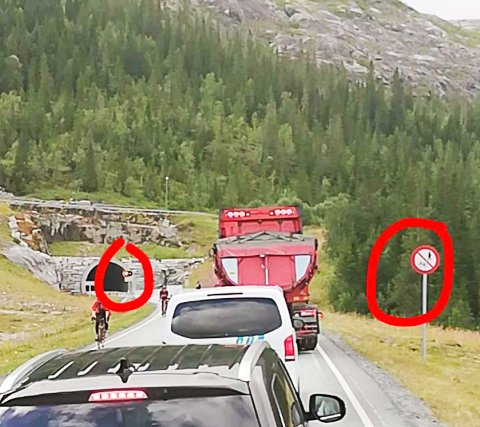 Ventetid: Her kommer de to syklistene ut av tunnelen og forbi den lange bilkøen. Vår tipser har satt ring rundt forbudsskiltet og skiltet som varsler at bilistene må vente med å kjøre inn.