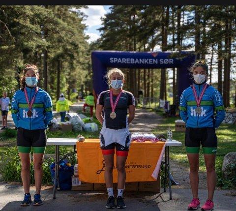 SEIER I KORONATID: Deltagerne slapp å konkurrere med maske, men på seierspallen måtte munnbindet på. Sara Magndal i midten flankert av søstrene Wultz fra Haugesund.