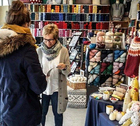 ALLE STRIKKER: Mona Olsen i Sarpsborg Garn & Broderi hjelper en kunde å finne et nytt strikkeprosjekt.