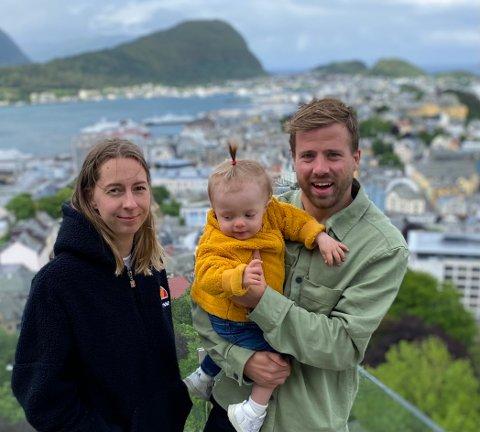 Samboerparet Oda Gjevik og Simen Rafn med lille Hedda, foran den storslåtte utsikten i Ålesund.
