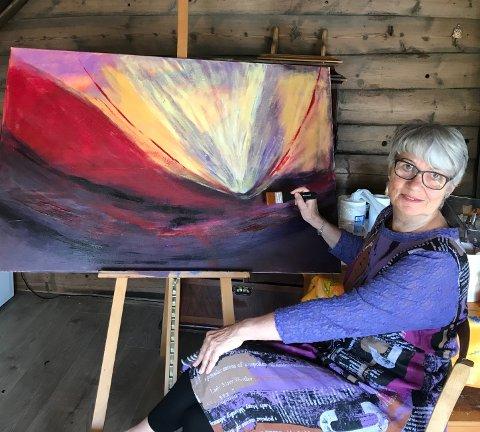AKRYL: Her er Eva Tofte fotografert i gamlehuset på Dyrnes medan ho er i arbeid med eit fargesterkt bilde. (Privat foto).