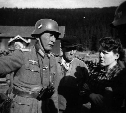 TOK KAMPEN: Olaug Karlsen diskuterer med kaptein Lehmann på Nordre Granum gård i Fall i april 1940 for å få han til å ikke henrette de ti fangene, slik som Peder Kleven i bakgrunnen. Bildet er tatt av en tysk soldat.