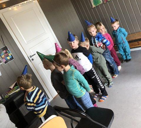 Spente og bursdagsklare barn på rekke og rad.