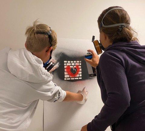 Kunstverk i musikkstudio: Oliver Stokke fikk sin graffitisjablong på veggen i musikkstudioet til Lier kulturskole under sommerskolen i StreetArt. Her får han hjelp av kurslærer Svanhild Rohdin.