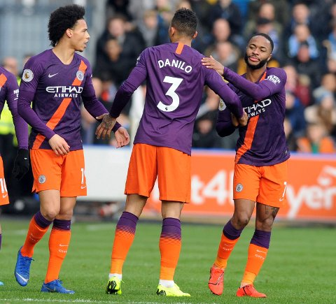 Manchester City's Danilo, center, celebrates with his teammates Leroy Sane, left, and Raheem Sterling, after scoring the opening goal for his team, during the English Premier League soccer match between Huddersfield Town and Manchester City at John Smith's stadium in Huddersfield, England, Sunday, Jan. 20, 2019. (AP Photo/Rui Vieira)