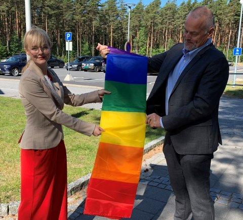 Ordfører Mona Vauger og kirkeverge Jan Heier heiser regnbueflagget på rådhuset på Hvaler