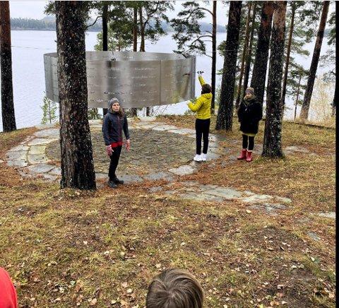 UTØYA: Elev Oliver Kjøniksen i klasse 10B på Vestsiden ungdomsskole henger opp ei rose ved minnesmerket på Utøya. På bildet ser vi også  Inga Marie Nymo Riset, rådgiver ved Det Europeiske Wergelandsenteret og Ingrid Kristine Børset, som underviser på Utøya.