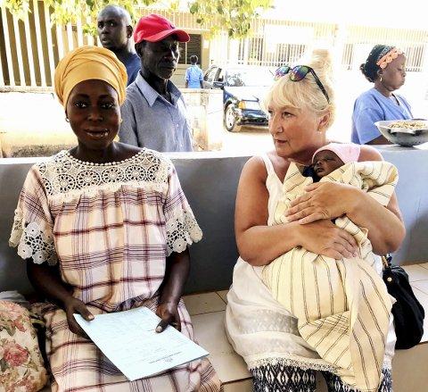 JORDMORKOS: Jordmor Bente Moum har fått låne babyen mens hun snakker med mora. Foto: Kirsti Vikhammer.
