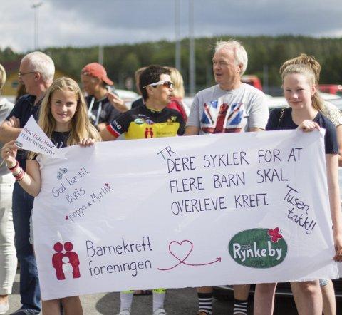 TUSEN TAKK! Mange stilte opp da Team Rynkeby Østfold startet sykkelrittet fra Halden fredag formiddag. Nora Hjelkrem (venstre) og Julie Kviem holder banneret.