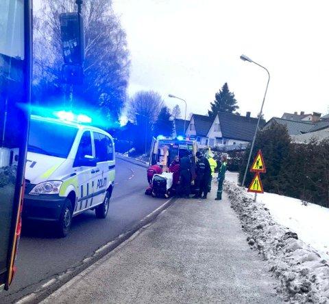 DRAMATISK: Etter å ha kommet seg ut i snøen slokket flammene. Her får mannen hjelp av politiet inn i ambulansen. Bussen skal ha stoppet i Sagdalen. FOTO: PRIVAT