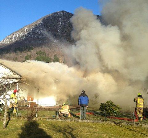 STOR RØYKUTVIKLING: Brannvesenet er framme på staden, og det er stor røykutvikling i bustaden.