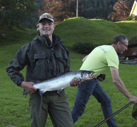 I sommar fekk også ungdommar prøve seg på laksefiske ved Osfossen. Her: Petter Porten (15) med den første fisken, og elveeigar Harald Lervik i bakgrunnen.