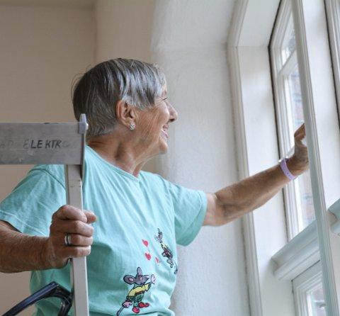Vask: Torhild Nøsted vaskar vindauge med eit smil om munnen.