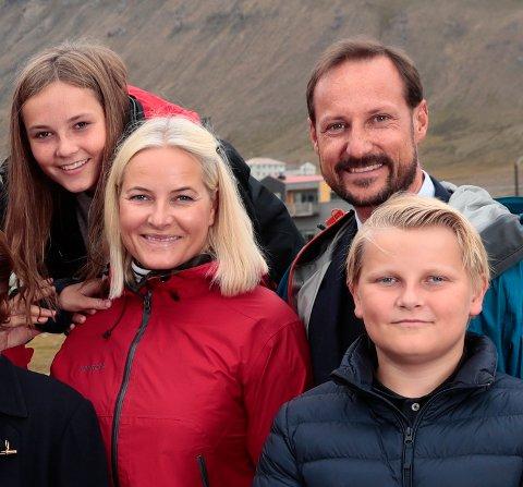 Prins Sverre Magnus, kronprins Haakon, kronprinsesse Mette-Marit og prinsesse Ingrid Alexandra smiler til fotografen under et besøk på Svalbard i sommer.