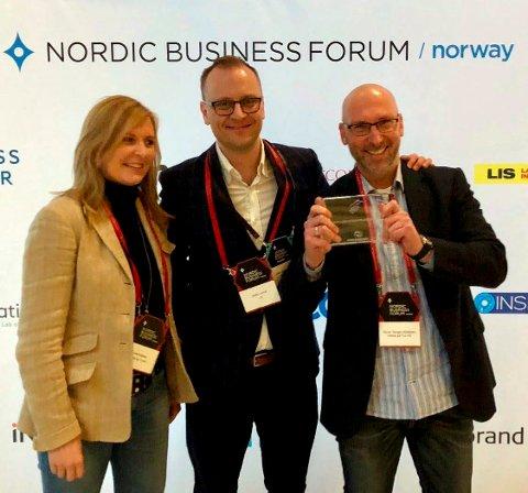 STOLT: Anette og Rune Kjeldsen mottok prisen i Oslo mandag av juryformann Steffen Larvoll (i midten).