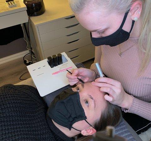 Natalie Matre frå Rosendal har starta eit heimestudio for bryn- og vippestyling. Her er ho under arbeid med ein kunde.
