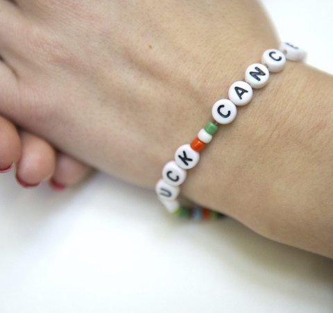På armen til Marte finner man en klar melding til sykdommen. «Fuck cancer». Den kjøpte bestevenninnen min til meg fra, kreftforeningen, sier hun.