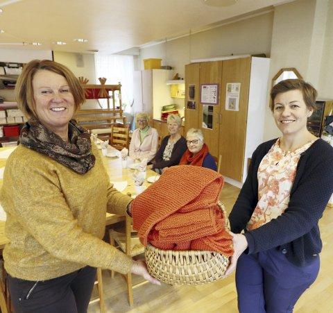 Vær så god: Daglig leder Arnhild Rustan ved Kjærsenteret kunne på vegne av brukere som har strikket, overlevere 13 oransje skjerf til fagleder Bente Charlotte Gausen ved Kirkens Bymisjon. Foto: Pål Nordby