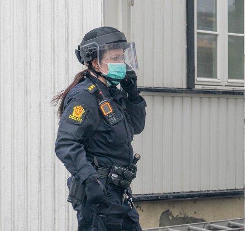 BESKYTTET: Politiet har sett seg nødt til å beskytte seg med streng smittevernbekledning. Her fra en politiaksjon i Drammen sentrum tidligere i vår.