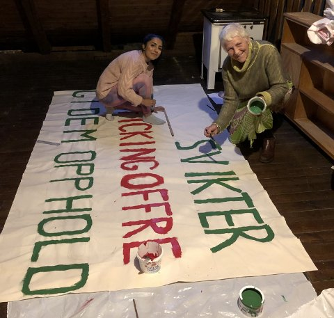 Mona Sharma (23) og Agnete Strøm (77) legger siste strøk på parolen. — Siste ordet vi maler og første i setningen, er selvsagt Norge, sier Strøm.