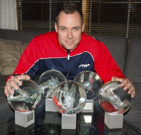 GLASKULER: Tommy Urhaug med fem av dei seks glaskulene han har fått som årets funksjonshemma utøvar på Idrettsgallaen. Den sjette kula står heime hjå faren Lyder Urhaug.