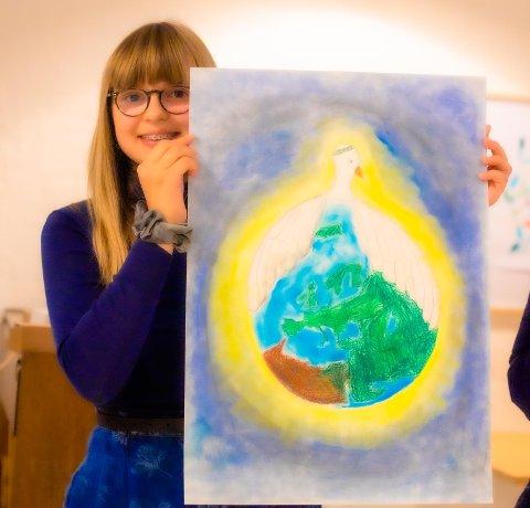 Frida Elen (12) fra Åsgård skole med sin tegning hvor bildet viser en fredsdue med vingene rundt jorda. Fredsduen forbarmer seg over jorda. Det gule lyset fra sola flyter så fint over i den blå himmelen. Det er et originalt, kunstnerisk og fint utført bilde, skriver juryen i sin bedømmelse.