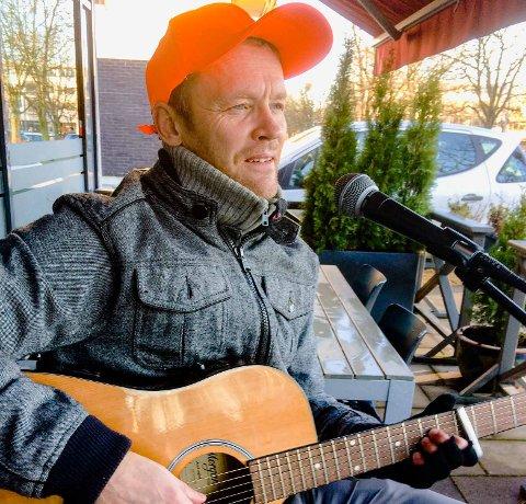 PÅ PLASS: Håvard Viumdal er som et lys i Ås' gater. Her lyser han opp med sang og gitarspill utenfor ved Ås kafé.